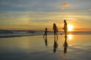 family happily playing on the beach at sunset for impute income to Mother on welfare case