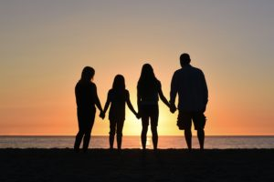family holding hands together gazing at the sunset