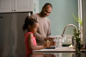 parent washing dishes with child for Adopt a Stepchild in Ca case